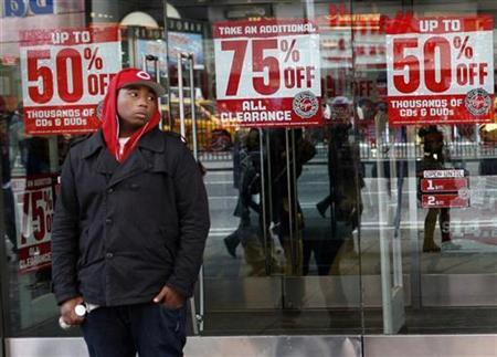 A shopper stands near sale signs outside the Virgin Megastore in New York's Times Square, December 26, 2008. REUTERS/Mike Segar