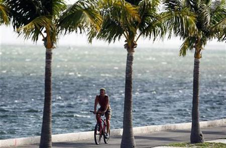 A resident rides a bike near the ocean in Key West, Florida as Hurricane Ike approaches September 7, 2008. REUTERS/Carlos Barria