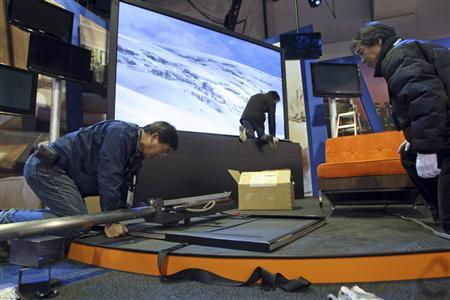 Panasonic Electronics technicians set up a display of flat panel televisions for the 2009 International Consumer Electronics Show at the Las Vegas Convention Center in Las Vegas, Nevada January 5, 2009. In the background is the 150-inch plasma television which was introduced at last year's show. The consumer technology trade show begins January 8 and is expected to attract 2,700 exhibitors and 130,000 attendees. REUTERS/Las Vegas Sun/Steve Marcus
