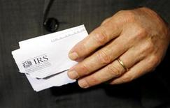<p>Holding a tax rebate letter from the Internal Revenue Service, President George W. Bush speaks about the economy during a visit to a small business in Sterling, Virginia March 26, 2006. REUTERS/Kevin Lamarque</p>