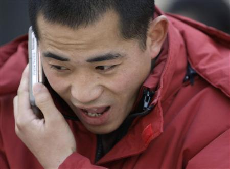 A man uses his mobile phone at Beijing's Wangfujing Street January 7, 2009. REUTERS/Jason Lee