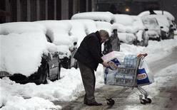 <p>Un uomo scarica la spesa dal carrello in una strada innevata di Milano. REUTERS/Stefano Rellandini</p>