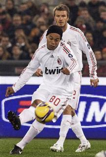 AC Milan's David Beckham (2nd L) watches his teammate Ronaldinho kicking a ball during their Italian Serie A soccer match against AS Roma at the Olympic stadium in Rome January 11, 2009. REUTERS/Alessandro Bianchi