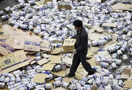 An officer prepares to destroy unqualified milk powder which was confiscated, in Shanghai November 14, 2008. REUTERS/Stringer