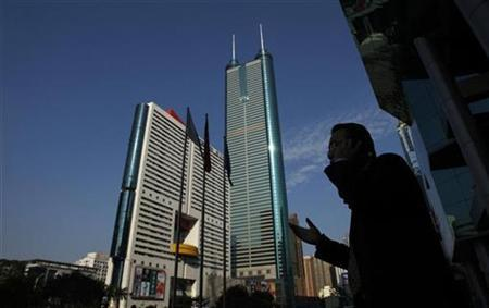 A man talks on the mobile phone outside the Shenzhen Stocks Exchange opposite to the 384-metre (1,260 ft) tall skyscraper at Shun Hing Square in the southern Chinese city of Shenzhen in Guangdong province November 25, 2008. REUTERS/Bobby Yip