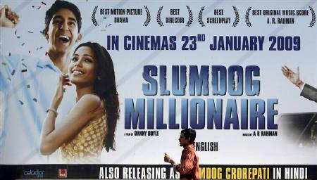 A man walks past a billboard displaying a poster of the film ''Slumdog Millionaire'' in Mumbai in this January 20, 2009 file photo. REUTERS/Punit Paranjpe