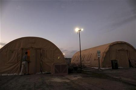 In this photo reviewed by the U.S. Military, a journalist enters the shower tent at Camp Justice, the location of the U.S. Military Commissions, at the U.S. Naval Base in Guantanamo Bay January 21, 2009. REUTERS/Brennan Linsley/Pool