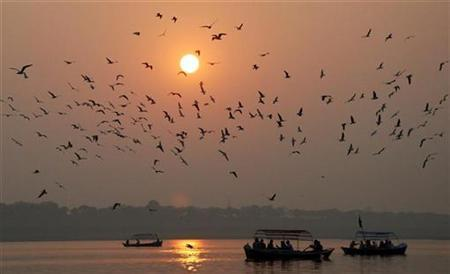 People travel in boats as the sun sets for the last time in 2008 over the banks of river Ganges in the northern Indian city of Allahabad December 31, 2008. REUTERS/Jitendra Prakash