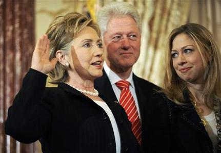 Secretary of State Hillary Clinton (L) is joined by her husband former President Bill Clinton and daughter Chelsea Clinton as she is ceremonially sworn in at the State Department in Washington, February 2, 2009. REUTERS/Jonathan Ernst