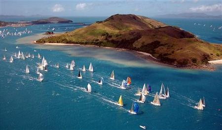 Yachts competing in the Premier Cruising section sail around Dent Island during day six of the Hamilton Island race week at Hamilton Island in Queensland August 26, 2005. REUTERS/Jack Atley/Handout