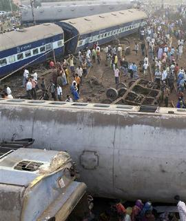 Onlookers stand beside the wreckage of a derailed train near the remote Jajpur Road station, about 120 km east of Bhubaneswar, February 14, 2009. REUTERS/Sanjib Mukherjee