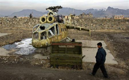 An Afghan boy walks by a destroyed Soviet made helicopter in Kabul in this picture taken February 5, 2009. REUTERS/Ahmad Masood