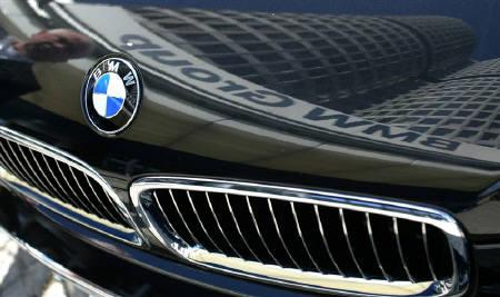 The headquarters of German luxury car maker BMW AG is reflected in a BMW car in Munich in this March 17, 2004 file photo. REUTERS/Alexandra Winkler/Files