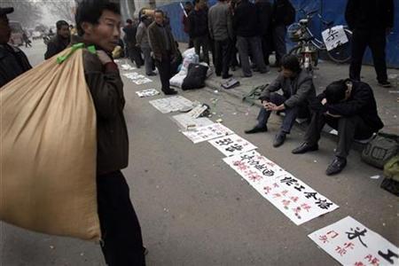 A jobseeker (L) walks by as others wait next to paper sheets describing their skills at a makeshift job market in Zhengzhou, Henan province February 12, 2009. REUTERS/Nir Elias