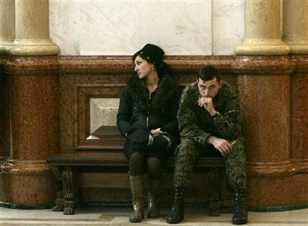 A woman and a soldier attend a religious service commemorating victims of last year's Georgian-Russian war in Tbilisi February 18, 2009. REUTERS/David Mdzinarishvili