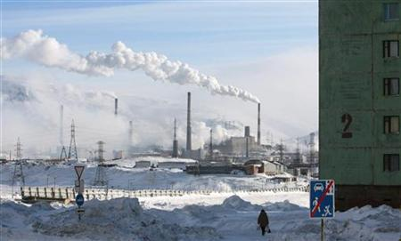 A woman walks near a nickel mine in the arctic city of Norilsk April 3, 2007. REUTERS/Denis Sinyakov