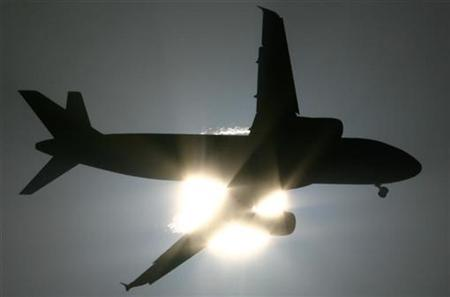 A passenger aircraft is silhouetted against the setting sun in New Delhi October 12, 2008. REUTERS/B Mathur