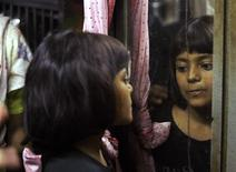"<p>Rubina Ali, who acted as the young Latika in the film ""Slumdog Millionaire"", looks at herself in a mirror at her uncle's residence in a slum in Mumbai February 20, 2009. REUTERS/Arko Datta</p>"