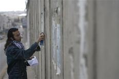 <p>Yusef Njm, artista dei graffiti palestinese, scrive i messaggi degli utenti sul muso tra Cisgiordania e Israele. REUTERS/Fadi Arouri (WEST BANK)</p>