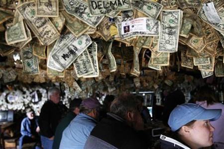 A patron sits underneath pinned mementos left on the ceiling of the Salty Dawg Saloon on the Homer Spit in Homer, Alaska, August 6, 2008. Tourists often write their names or hometowns on dollar bills to leave as souvenirs after visiting the bar. REUTERS/Lucas Jackson
