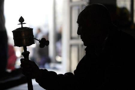 A Tibetan spins a prayer wheel during the third day of the Tibetan New Year at a community centre in Kathmandu February 27, 2009. REUTERS/Gopal Chitrakar