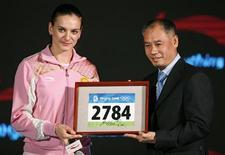<p>Russa recordista mundial do salto com vara Yelena Isinbayeva mostra seu número nos Jogos de Pequim ao lado de Li Ning, dono da empresa de material esportivo que vai patrocinar a atleta, em Pequim. REUTERS/Christina Hu</p>