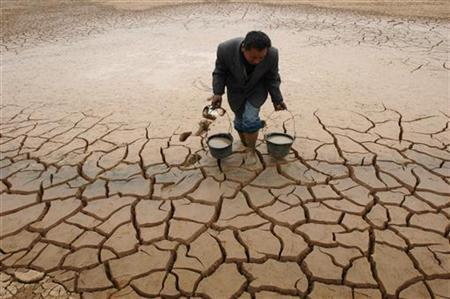 A farmer takes water from a dried-up pond to water his vegetable field on the outskirts of Yingtan, Jiangxi province December 10, 2007. REUTERS/Stringer