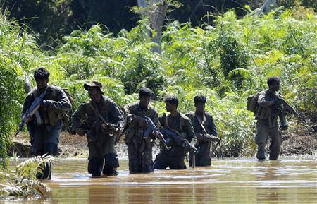 Sri Lanka soldiers patrol the Puthukkudiyirippu area, where fighting between the Sri Lanka army and the Liberation Tamil Tigers Eelam (LTTE) has taken place, in northeast Sri Lanka February 28, 2009. REUTERS/Stringer