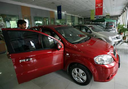 A worker opens the door of a new car on display at a showroom in Mumbai in this August 3, 2006 file photo. Car sales in India snapped a four-month slide in February, rising nearly 22 percent from a year ago, as banks lowered loan rates and firms passed on tax cuts, bolstering efforts to stem an economic slowdown. REUTERS/Punit Paranjpe