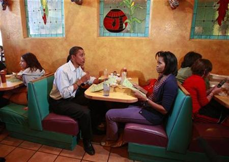 Then-U.S. Democratic presidential nominee Senator Barack Obama (D-IL) and his wife Michelle sit in a booth for a family meal with their daughters, Malia and Sasha (both obscured), at Jorge's Sombrero Mexican restaurant in Pueblo, Colorado in this file photo from November 1, 2008. REUTERS/Jason Reed