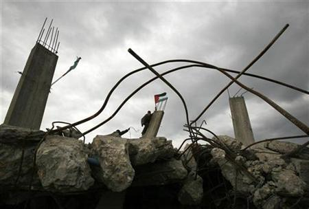 A Palestinian places a Palestinian flag atop the ruins of a house, destroyed during Israel's 22-day offensive, in Jabalya in the northern Gaza Strip March 2, 2009. REUTERS/Suhaib Salem