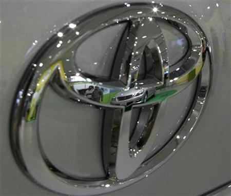 A vehicle and visitors are reflected on a Toyota Motor Corp logo at the Japanese automaker's showroom in Tokyo February 13, 2009. REUTERS/Yuriko Nakao