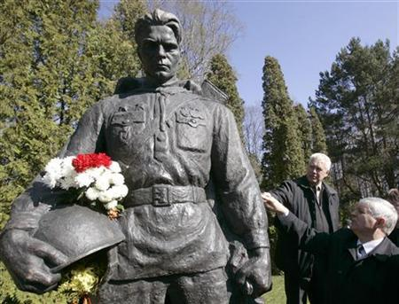 People inspect the bronze statue of World War Two Red Army soldier that was relocated from the city centre to a military cemetery in Tallinn in this file photo from May 1, 2007. REUTERS/Ints Kalnins
