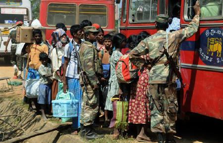 Ethnic Tamil civilians board a military vehicle to go to a camp for internally displaced people after being checked by the military in Vishvamadu, a town recently captured by soldiers battling to crush the Liberation Tigers of Tamil Eelam (LTTE), in this February 7, 2009 file photo. REUTERS/Stringer/Files