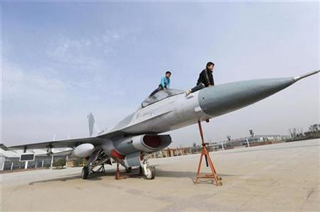 Children play on the replica of a F-16 fighter jet in front of an exhibition hall in Hefei, Anhui province, November 26, 2008.REUTERS/Jianan Yu