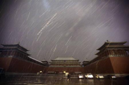 People walk past the Wumen Gate of the Forbidden City during a snowfall at night, in Beijing in this February 17, 2009 file photo. REUTERS/Jason Lee/Files