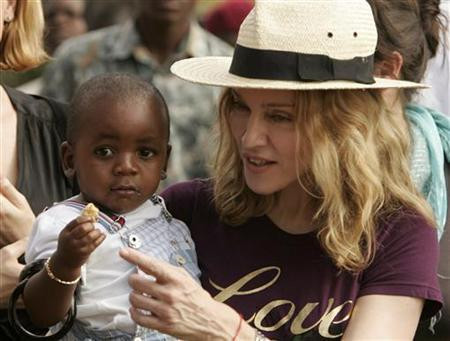 Madonna holds her adopted son, David Banda, at an orphan care centre run by Raising Malawi, a grassroots initiative by Madonna, in Mphendula Village, about 40 km (25 miles) from the capital Lilongwe in this file photo from April 19, 2007.REUTERS/Siphiwe Sibeko
