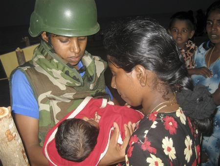A Sri Lankan Navy medical personnel (L) carries an injured Tamil baby at the Pulmudai temporary hospital in Trincomalee, about 257 km (160 miles) east of Colombo, March 16, 2009. REUTERS/Stringer