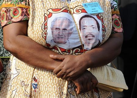 A woman wears a dress with images of Pope Benedict XVI (L) and Cameroon's President Paul Biya at the international airport in Yaounde March 17, 2009. REUTERS/Alessandro Bianchi