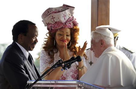Pope Benedict XVI speaks to Cameroon's President Paul Biya (L), as Biya's wife Chantal applauds, at the international airport in Yaounde March 17, 2009. REUTERS/Alessandro Bianchi