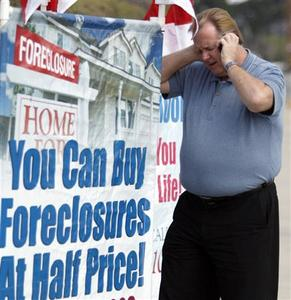 Home Center Realty owner Ron Barnard talks on his cell phone as he stands next to a sign advertising his business in Norco, California in this picture taken March 12, 2009. REUTERS/Lucy Nicholson