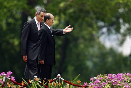 Singapore's Prime Minister Lee Hsien Loong (L) gestures for Myanmar's Prime Minister Thein Sein to enter an observation podium during a welcome ceremony at the Istana (Presidential residence) in Singapore March 17, 2009. REUTERS/Vivek Prakash