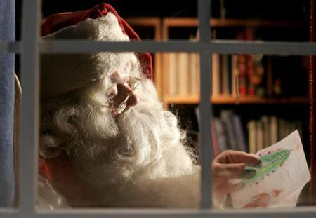 A man dressed as Santa Claus reads letters from children from around the world in his office at the Santa Claus' Village at the Arctic Circle near Rovaniemi, Finland. Picture taken December 18, 2007. REUTERS/Kacper Pempel