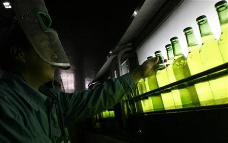A worker checks the quality of beer at a production line at the Snow Brewery in Shenyang, northeast China's Liaoning province February 2, 2007. REUTERS/Sheng Li