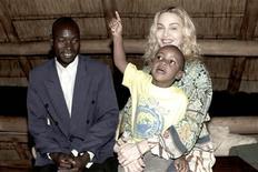"""<p>Foto publicitaria de Madonna con su hijo adoptivo David mientras visitan a su padre biológico Yohane Banda en Malaui, 31 mar 2009. Madonna """"no está eludiendo cuestiones legales"""" en el proceso de adoptar a una pequeña niña de Malaui, dijo el martes su portavoz, en medio de las críticas hacia la cantante estadounidense a quien algunos acusan de recibir un trato especial en el país del sudeste africano. REUTERS/Tom Munro/Warner Brothers Records</p>"""