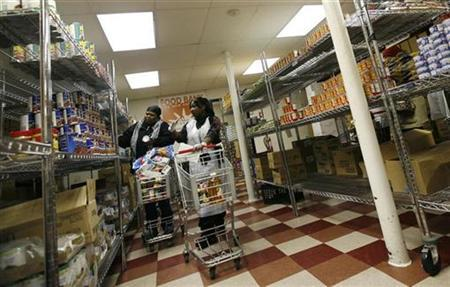 A woman shops with a staff member (R) at the Community Kitchen food pantry in the Harlem section of New York City December 10, 2008. REUTERS/Mike Segar