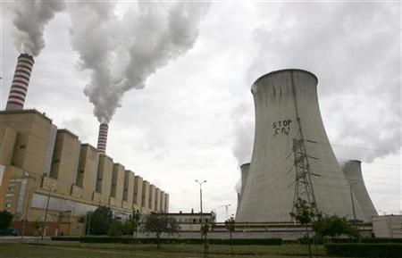 Greenpeace activists paint a slogan reading ''Stop CO2'' on the one of the smoke stacks at the Belchatow power plant in Rogowiec near Belchatow, about 177 km (110 miles) from Warsaw July 3, 2007. REUTERS/Kacper Pempel