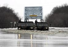 <p>Two U.S. National Guard vehicles drive through flood waters from the Red River after delivering sandbags for dike construction to a rural farm in Hendrum, Minnesota, March 30, 2009. REUTERS/Eric Miller</p>