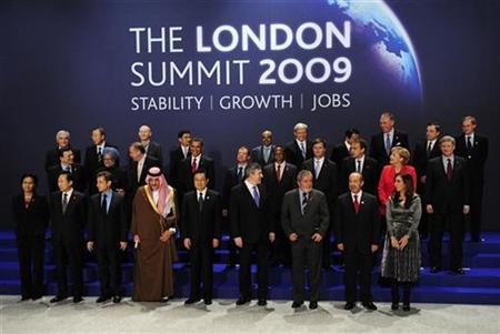 Britain's Prime Minister Gordon Brown (4th R) looks towards Canadian Prime Minister Stephen Harper (MIDDLE R), who missed the first family photograph shot earlier in the day, as they prepare to pose for a second family photograph at the G20 summit at the ExCel centre, in east London, April 2, 2009. REUTERS/Dylan Martinez