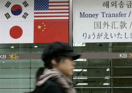 4月3日、韓国ウォンの下落を背景に美容整形を目的に同国を訪れる外国人が増加している。写真はソウルの銀行前を歩く女性。昨年11月撮影(2009年 ロイター/Jo Yong-Hak)